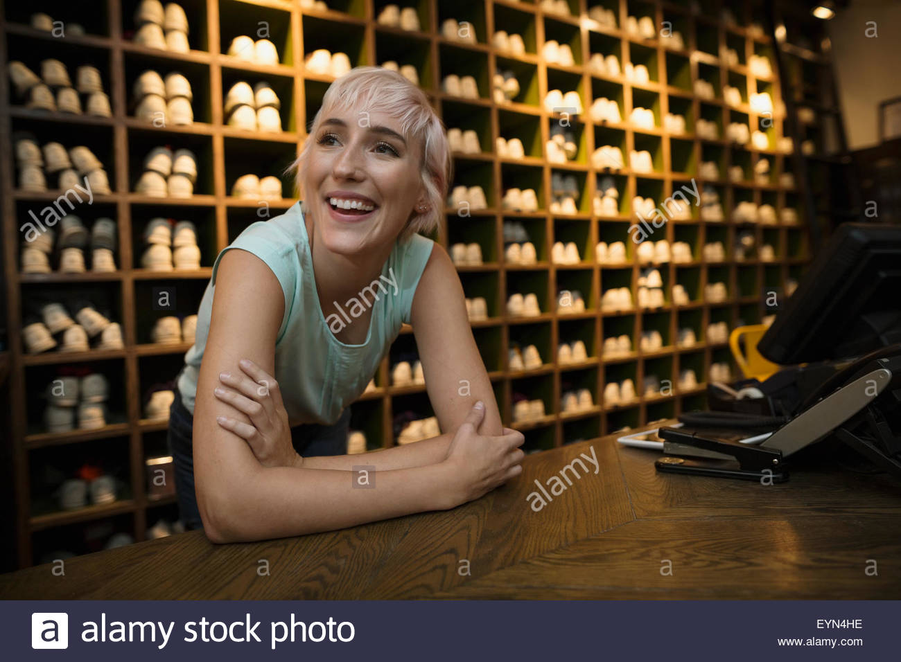 Smiling woman leaning on bowling shoes rental counter - Stock Image