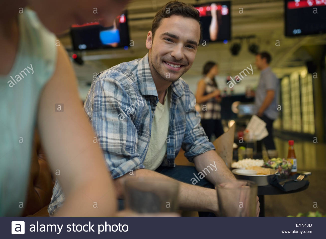 Portrait smiling young man with friends bowling alley Stock Photo
