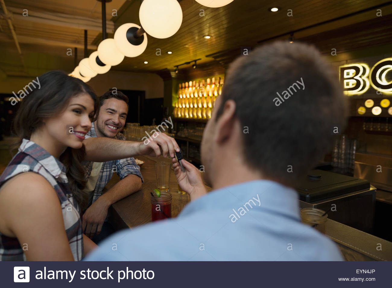 Friends drinking hanging out at bowling alley bar - Stock Image