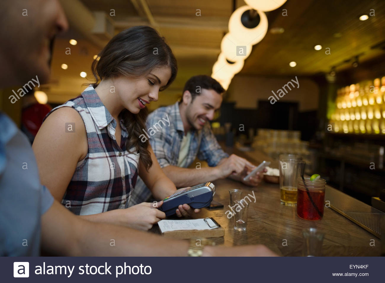 Friends paying for bar bill at bowling alley - Stock Image
