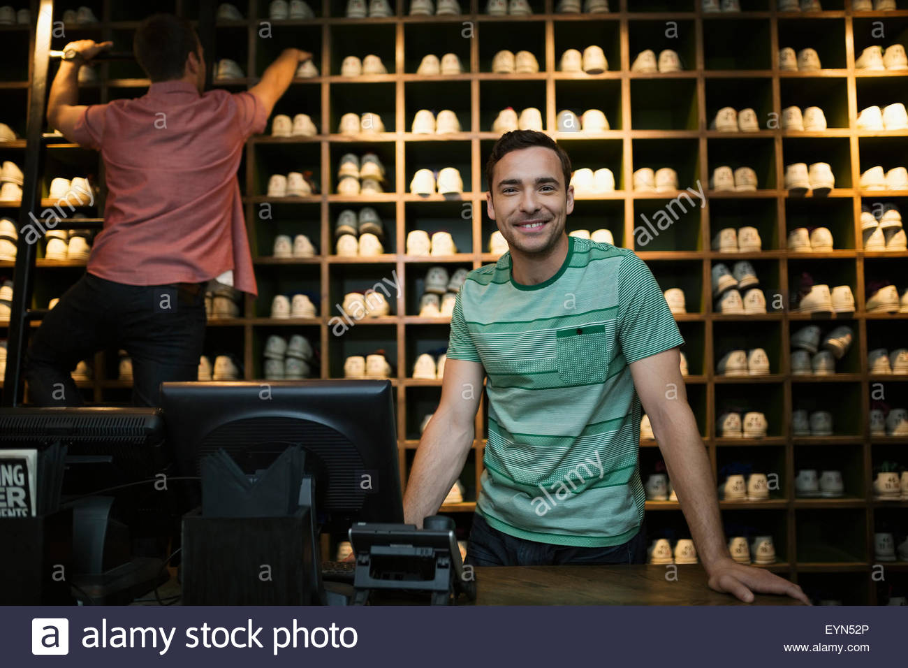 Portrait confident worker shoe rental counter bowling alley - Stock Image