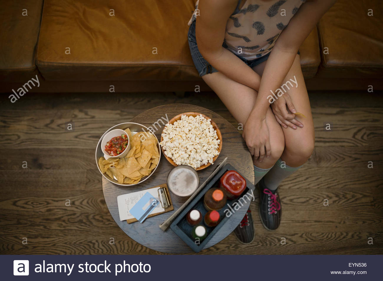 Overhead view young woman with snacks bowling alley - Stock Image