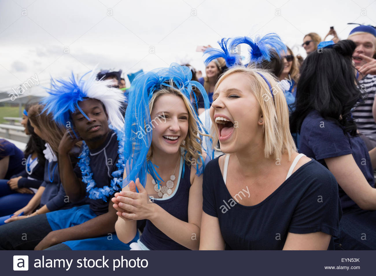 Enthusiastic woman screaming from bleachers at sports event - Stock Image