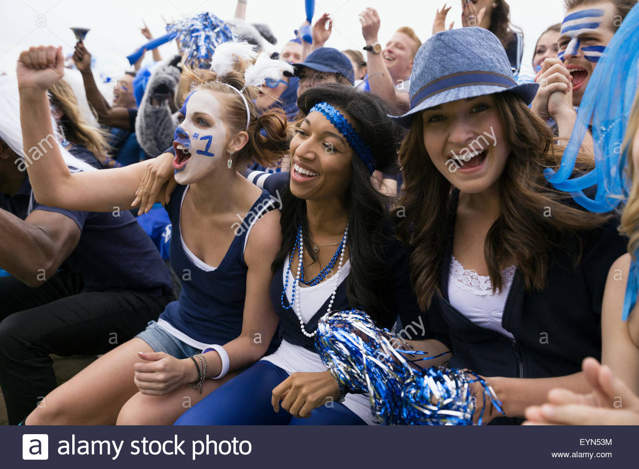 Enthusiastic fans in blue cheering bleachers sports event - Stock Image