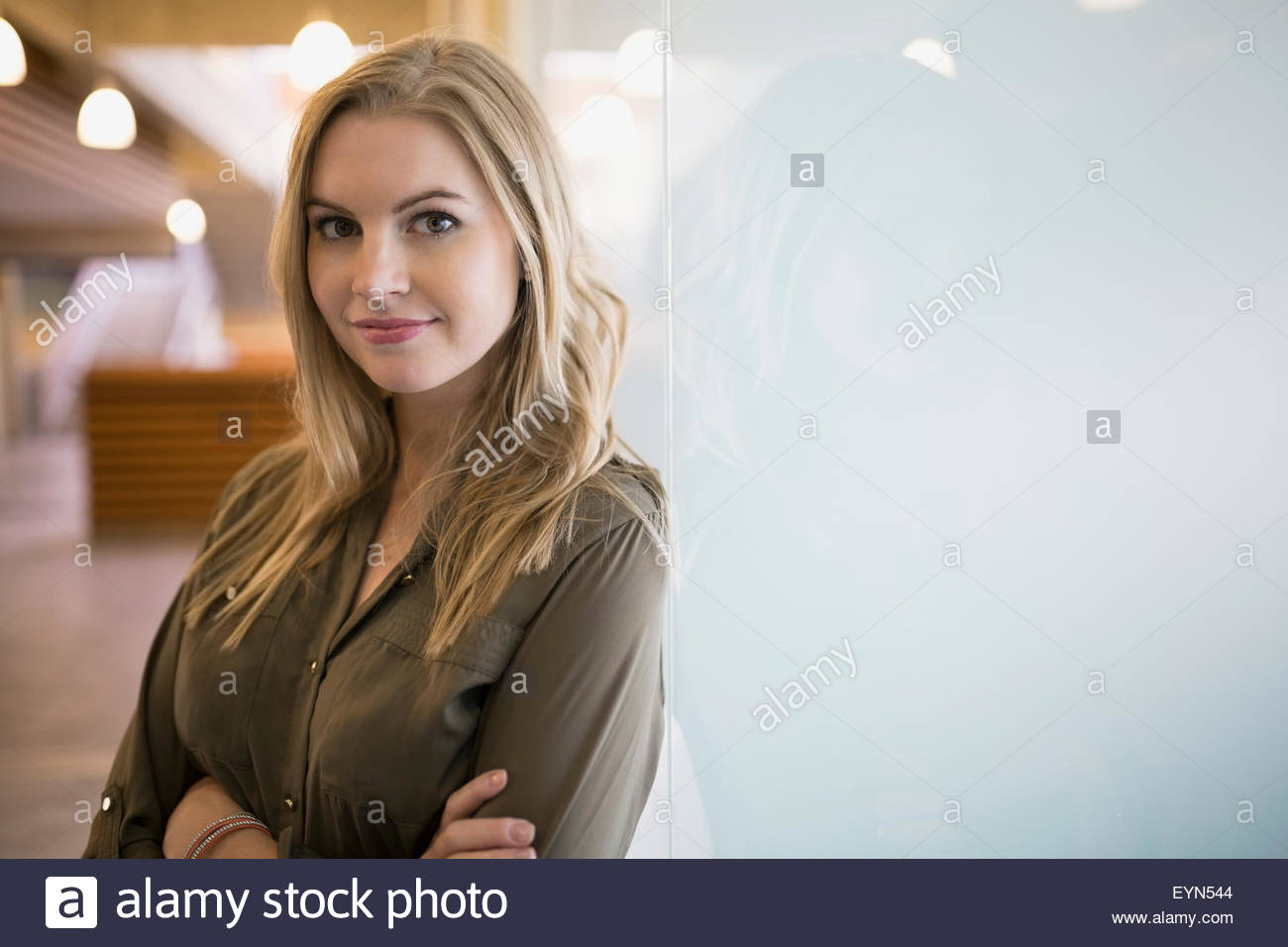 Portrait confident blonde businesswoman at frosted glass - Stock Image