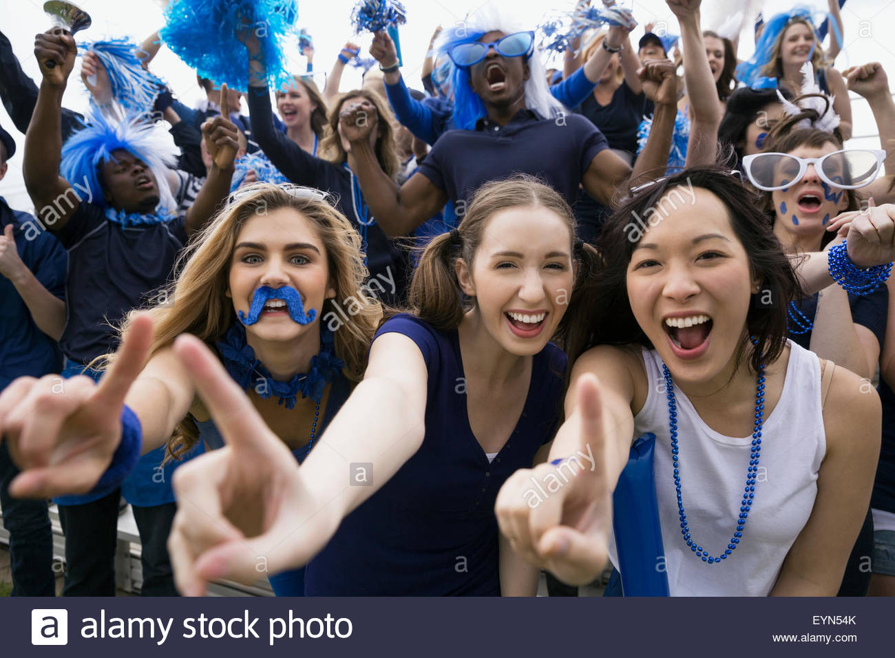 Portrait enthusiastic female fans gesturing number one bleachers - Stock Image