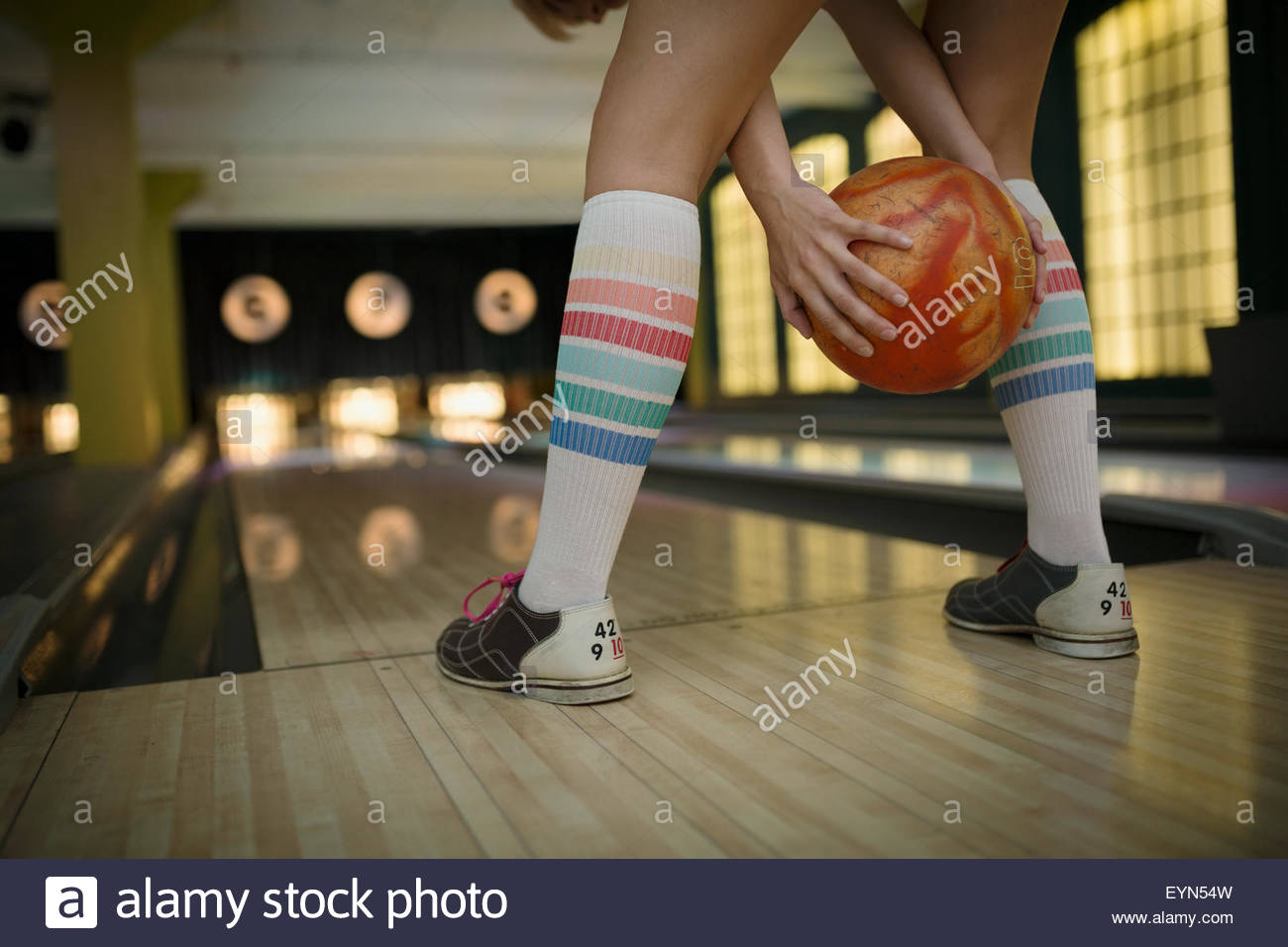 Young woman with knee-high socks bowling - Stock Image