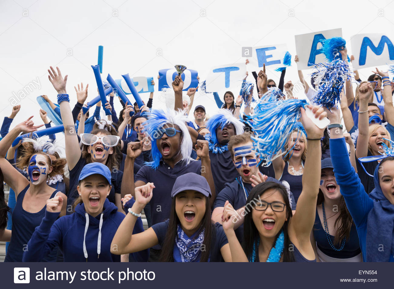 Portrait enthusiastic crowd in blue cheering sports event - Stock Image