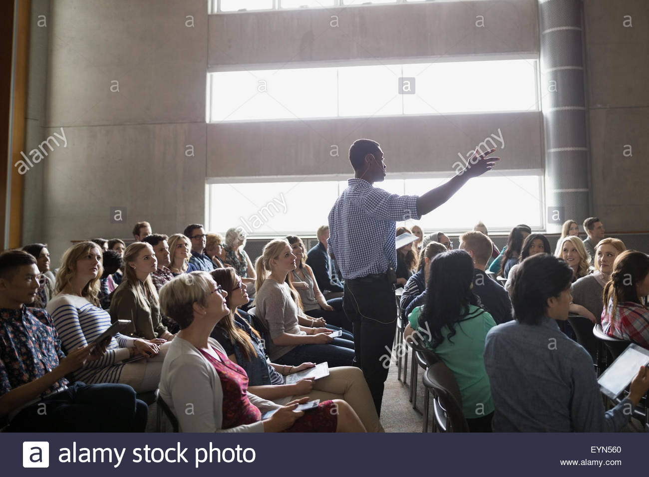 Professor giving lecture among auditorium audience - Stock Image
