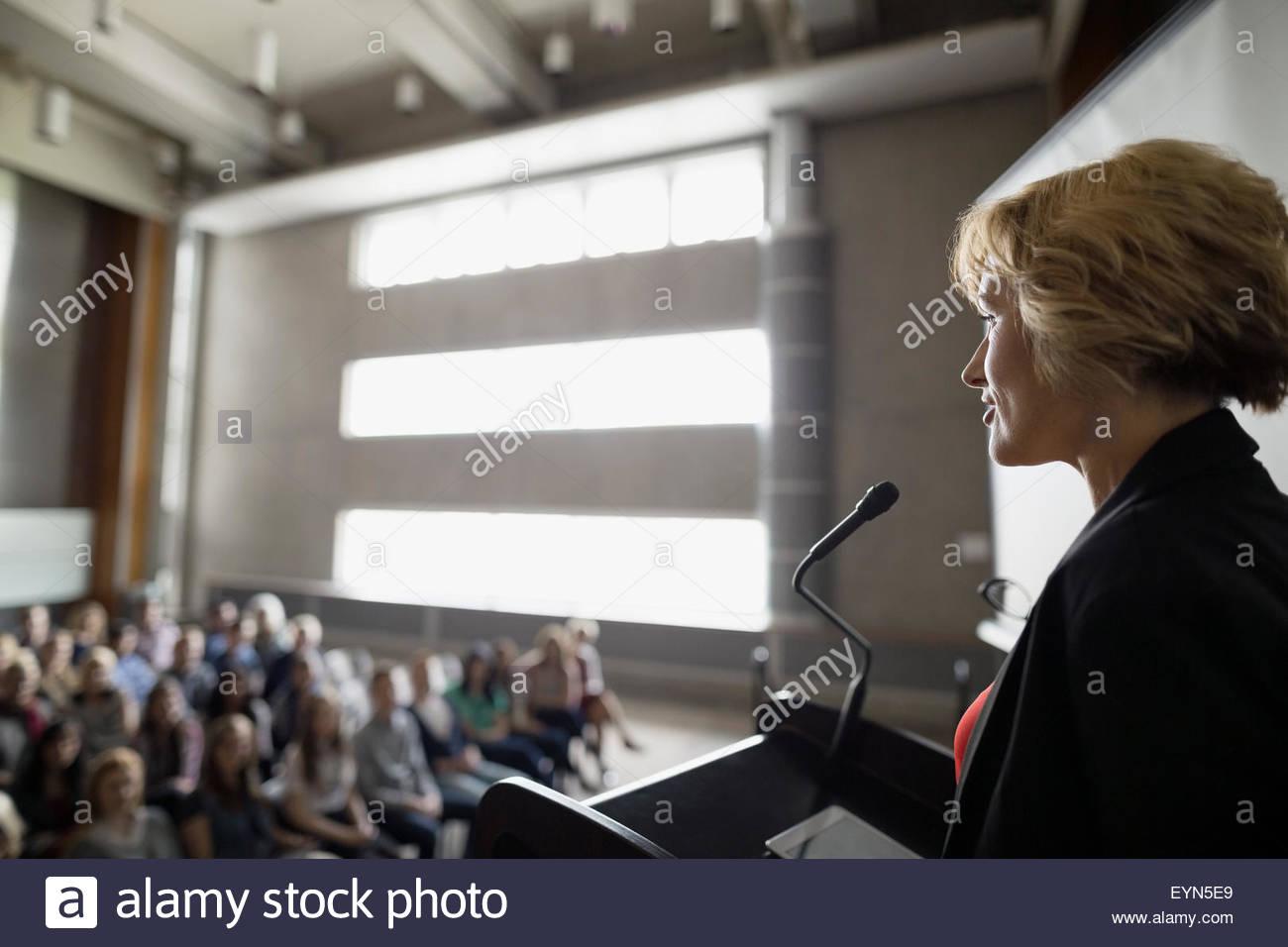 Professor speaking at podium to auditorium audience - Stock Image