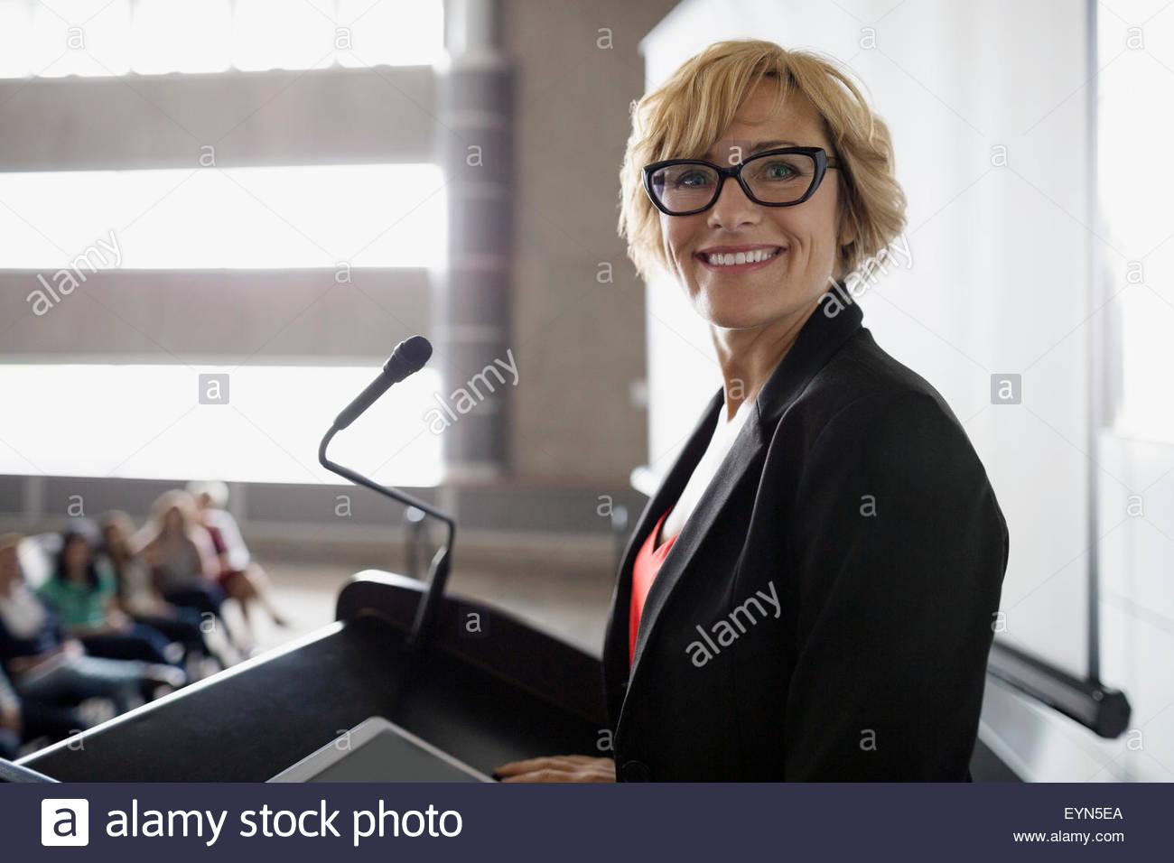 Portrait confident professor at podium in auditorium - Stock Image