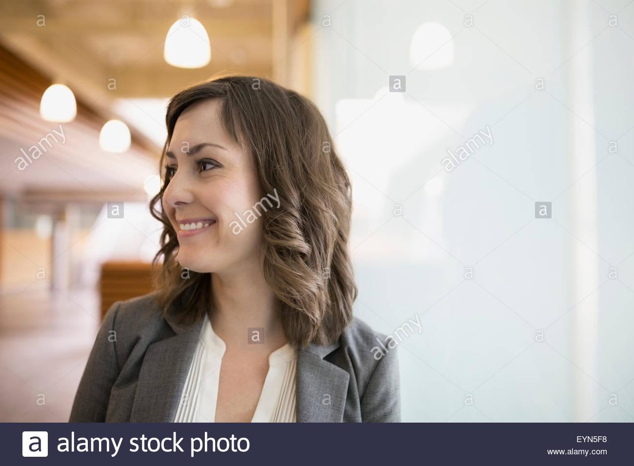 Portrait smiling brunette businesswoman looking away - Stock Image