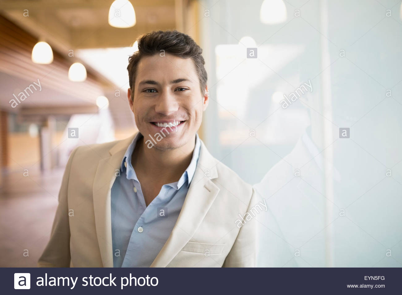 Portrait confident brunette businessman leaning frosted glass - Stock Image