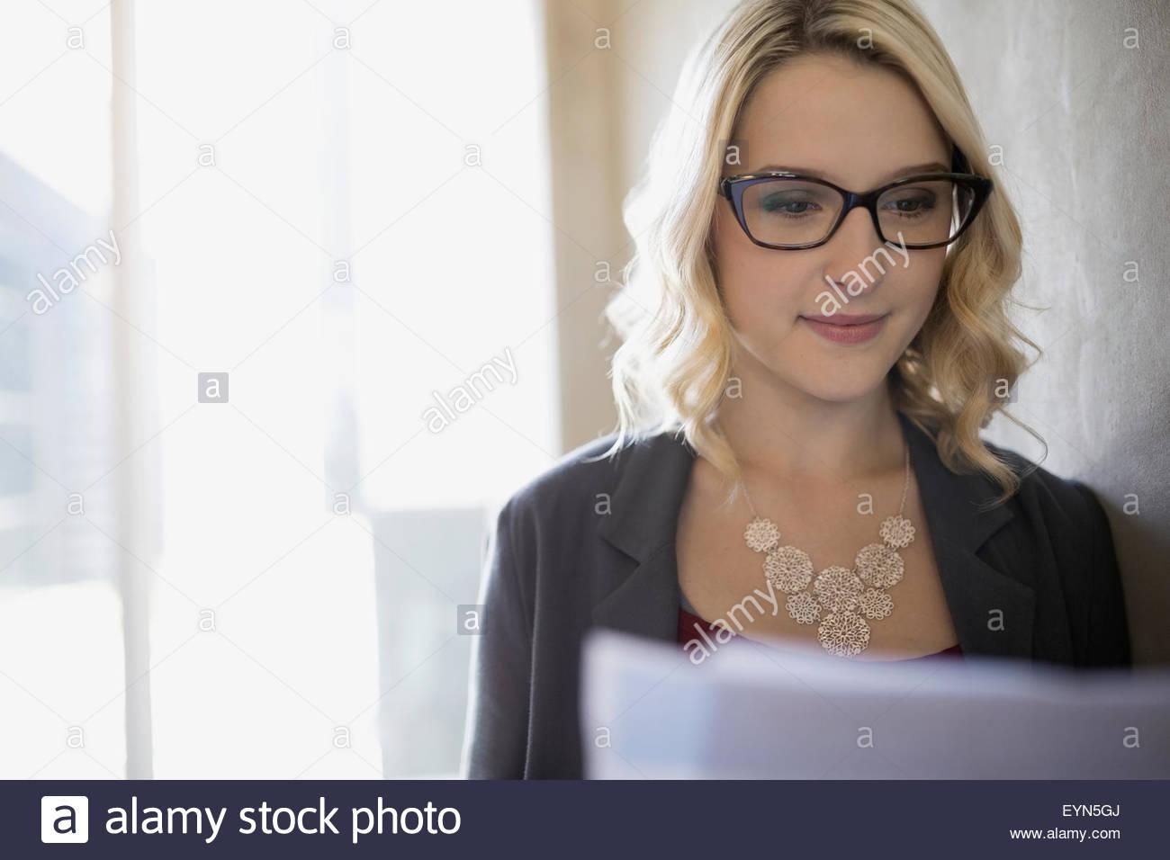 Focused blonde businesswoman reading paperwork - Stock Image