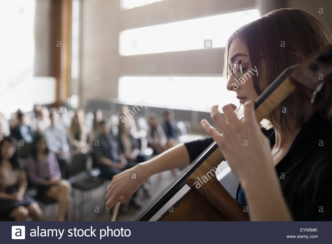 Female cellist performing for audience in auditorium - Stock Image