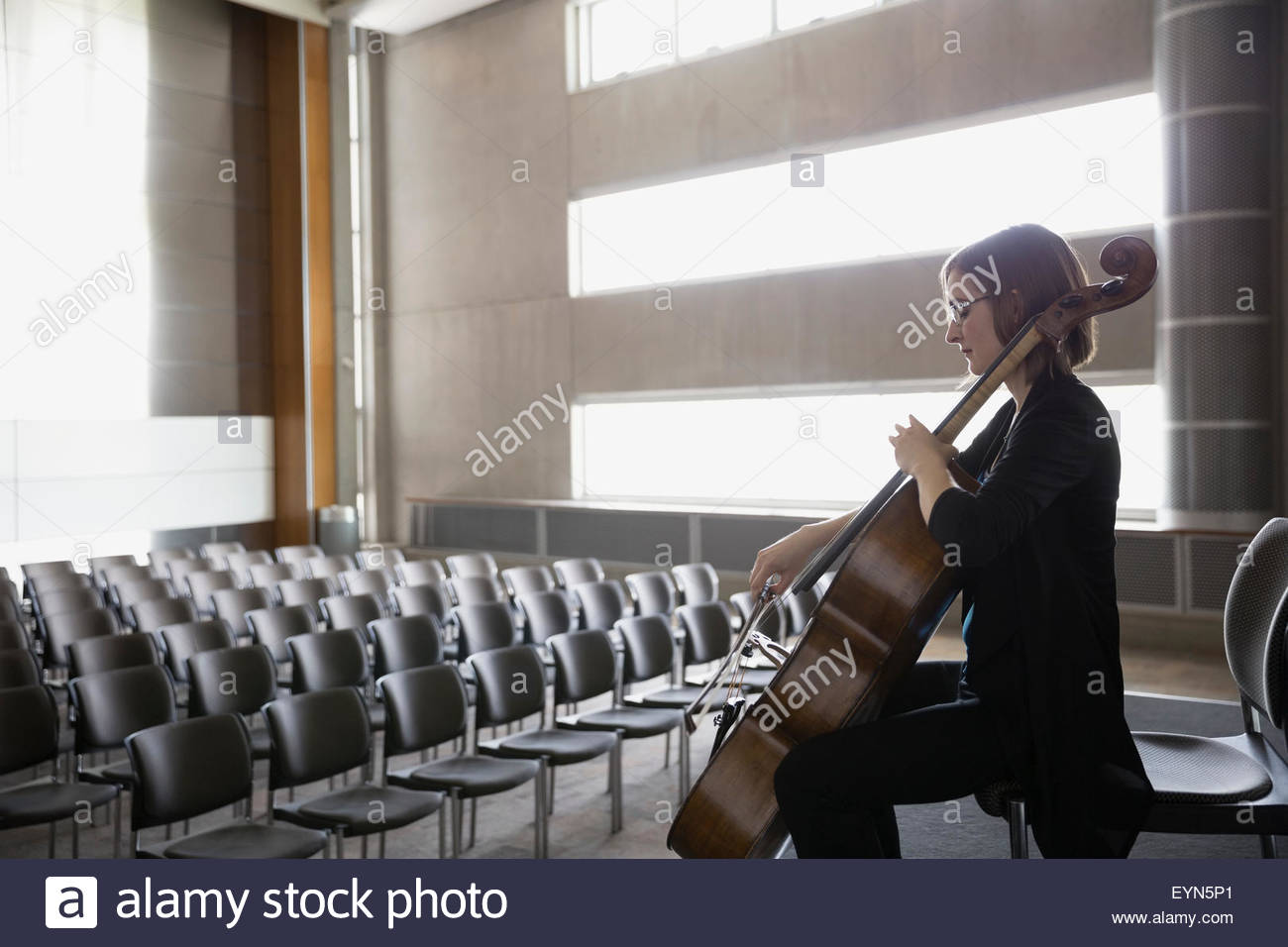 Female cellist practicing on stage in empty auditorium - Stock Image