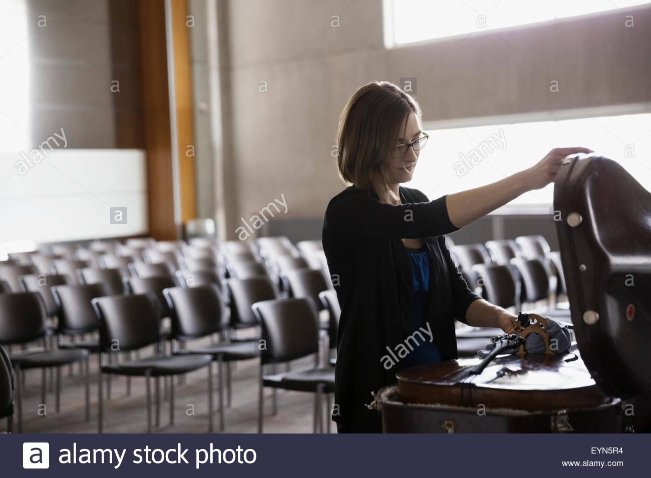 Female cellist opening cello case in auditorium - Stock Image