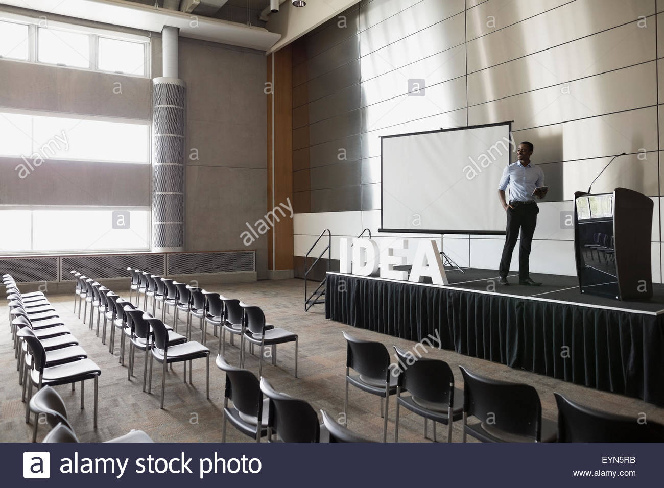 Man standing on stage in empty auditorium - Stock Image