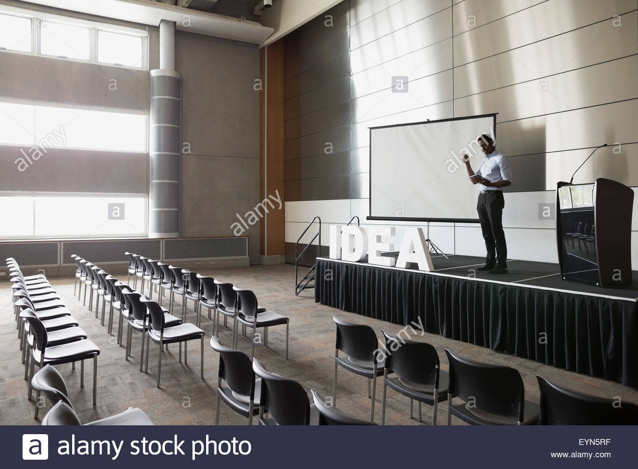 Man rehearsing on stage in empty auditorium - Stock Image