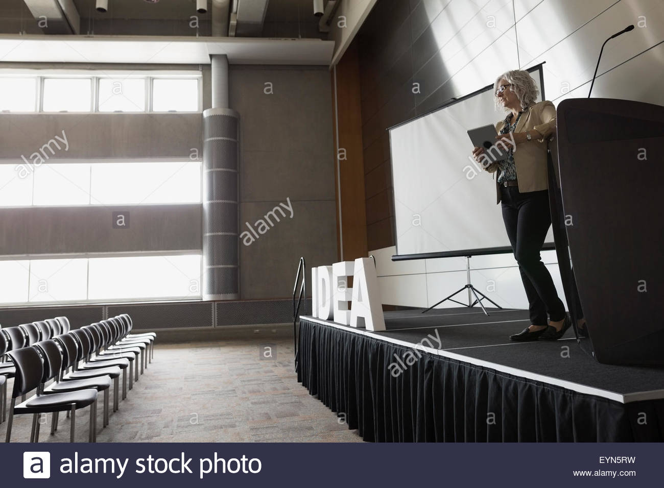 Woman with digital tablet on stage empty auditorium - Stock Image