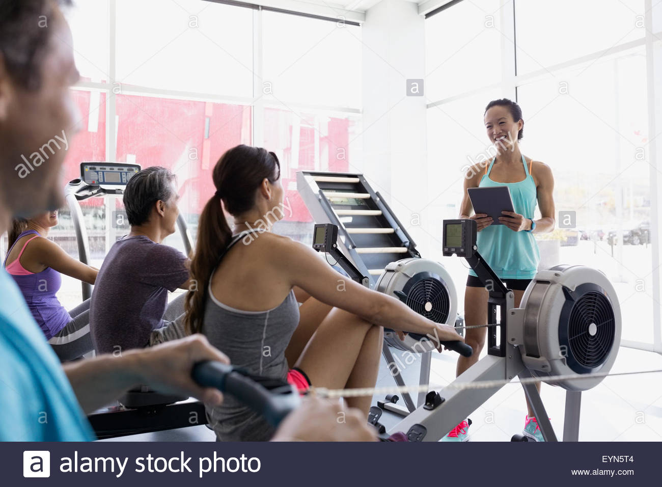 Fitness instructor with digital tablet guiding rowing class - Stock Image