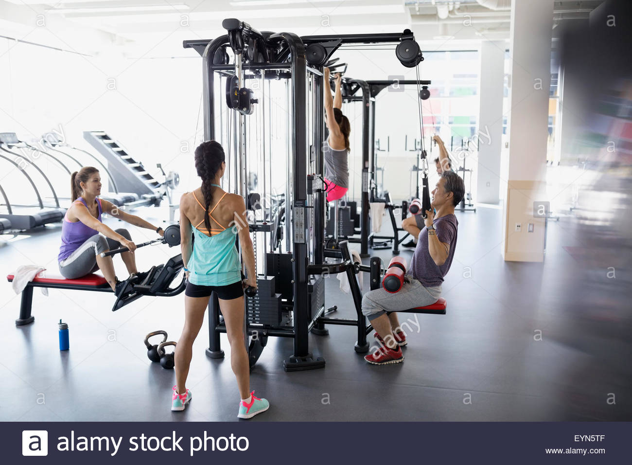 People working out on exercise equipment at gym Stock Photo