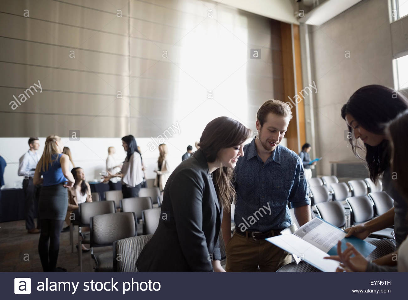 Students reviewing information in auditorium audience - Stock Image