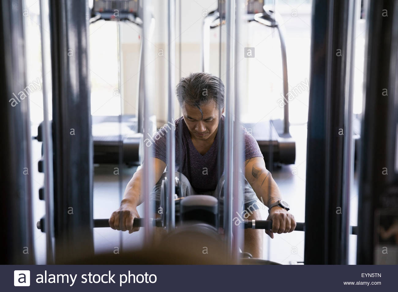 Determined man at seated cable row in gym - Stock Image