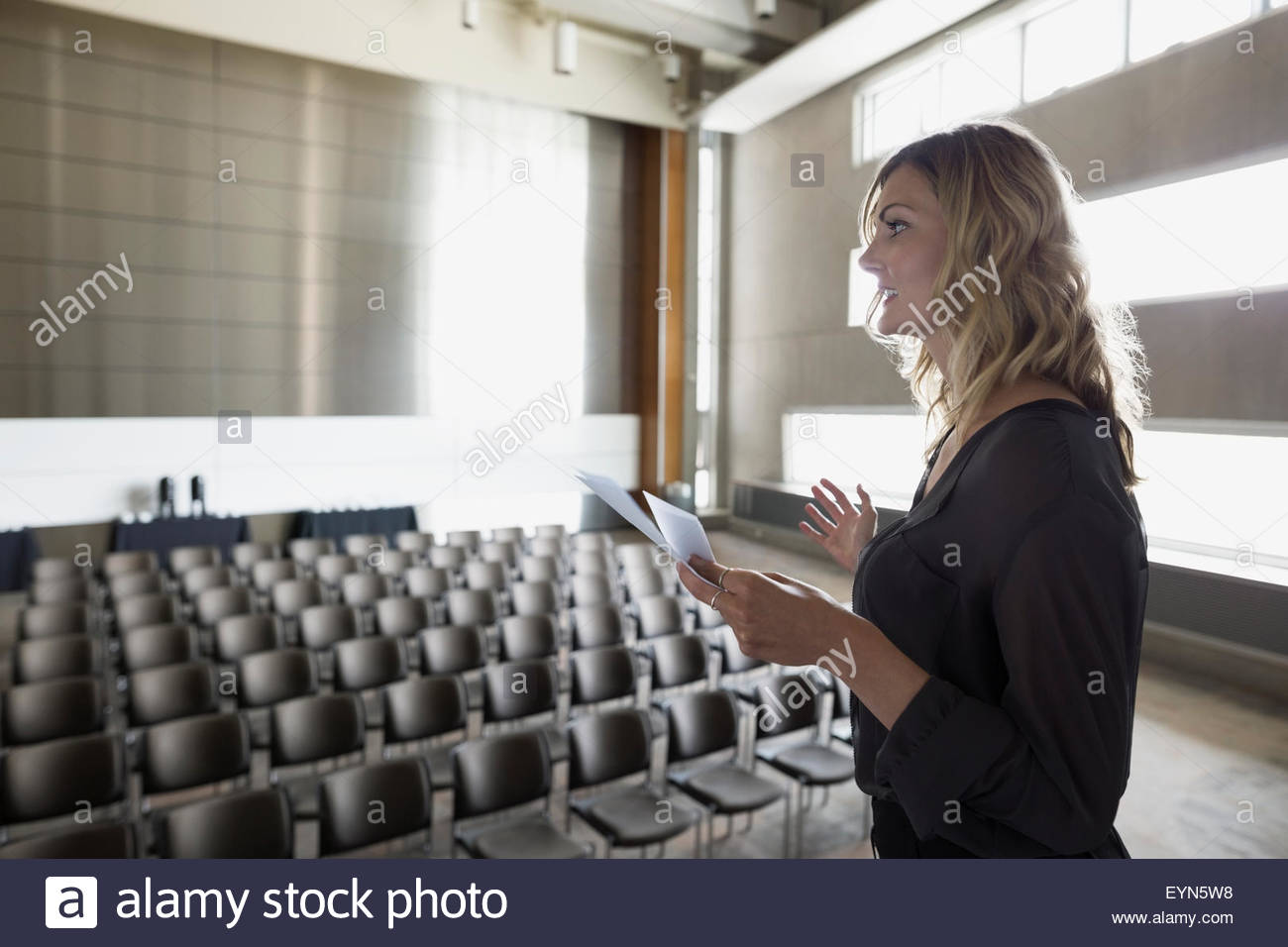 Woman reviewing notes on stage in empty auditorium - Stock Image