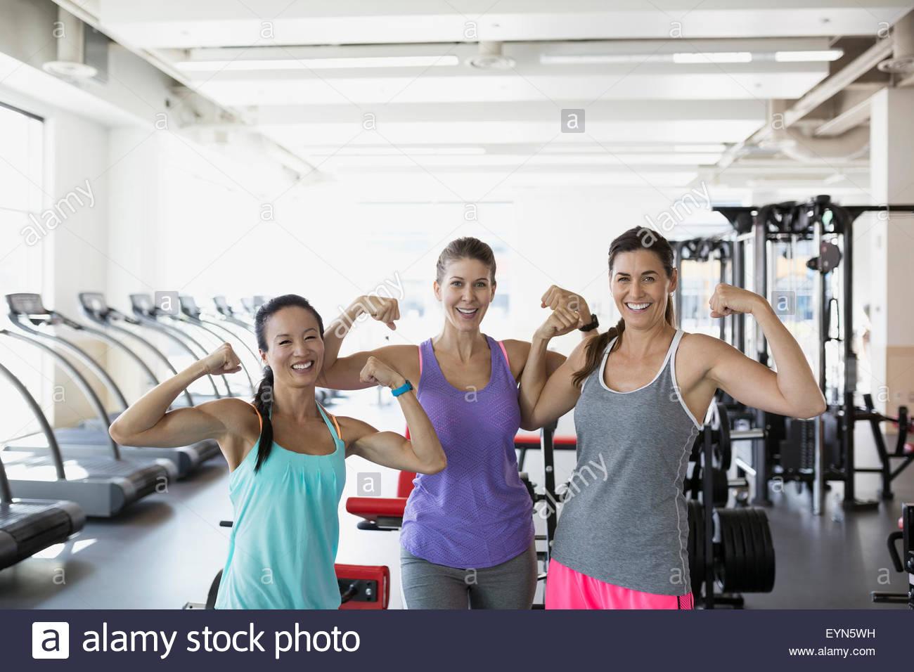 Portrait confident women flexing muscles at gym - Stock Image