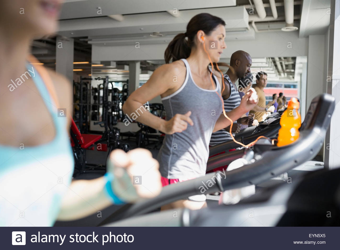 Determined woman running on treadmill at gym - Stock Image