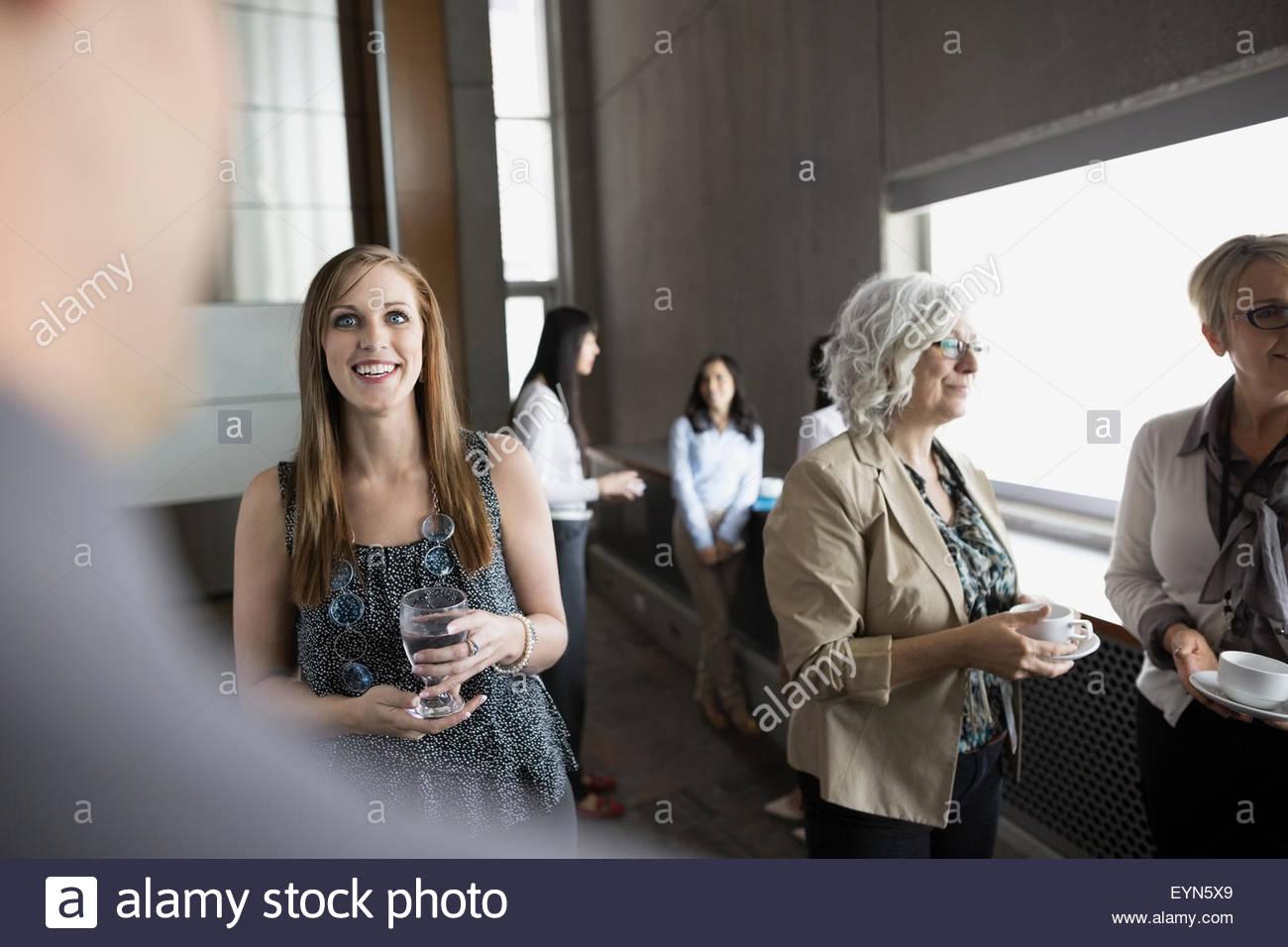 People socializing in auditorium - Stock Image