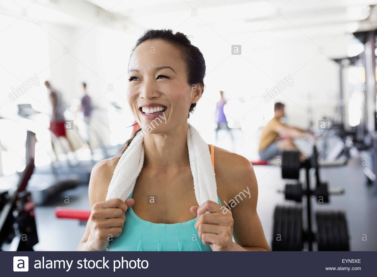 Portrait smiling woman with towel around neck gym - Stock Image