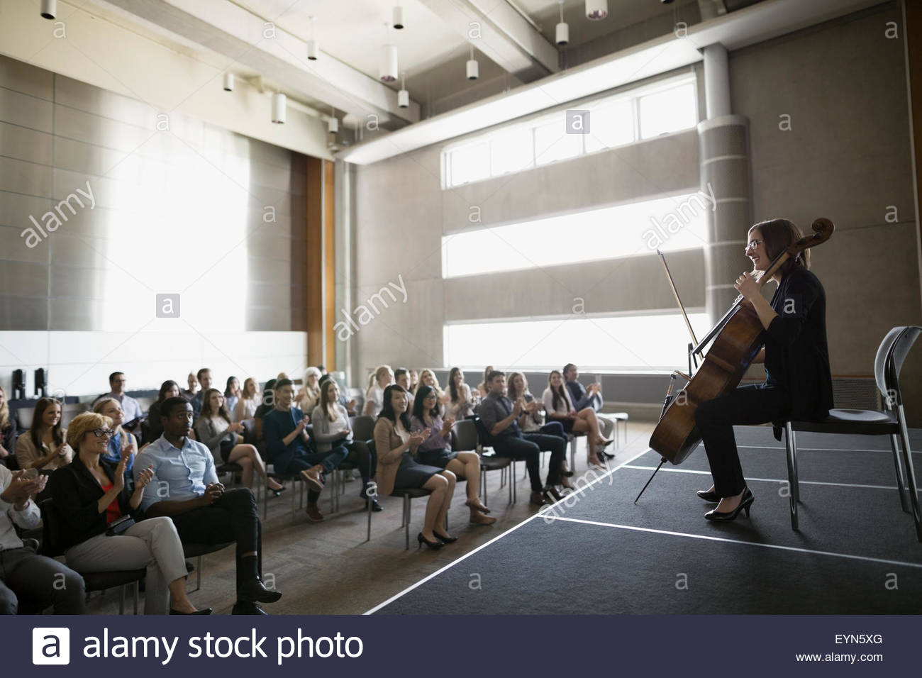 Audience watching female cellist perform on auditorium stage - Stock Image