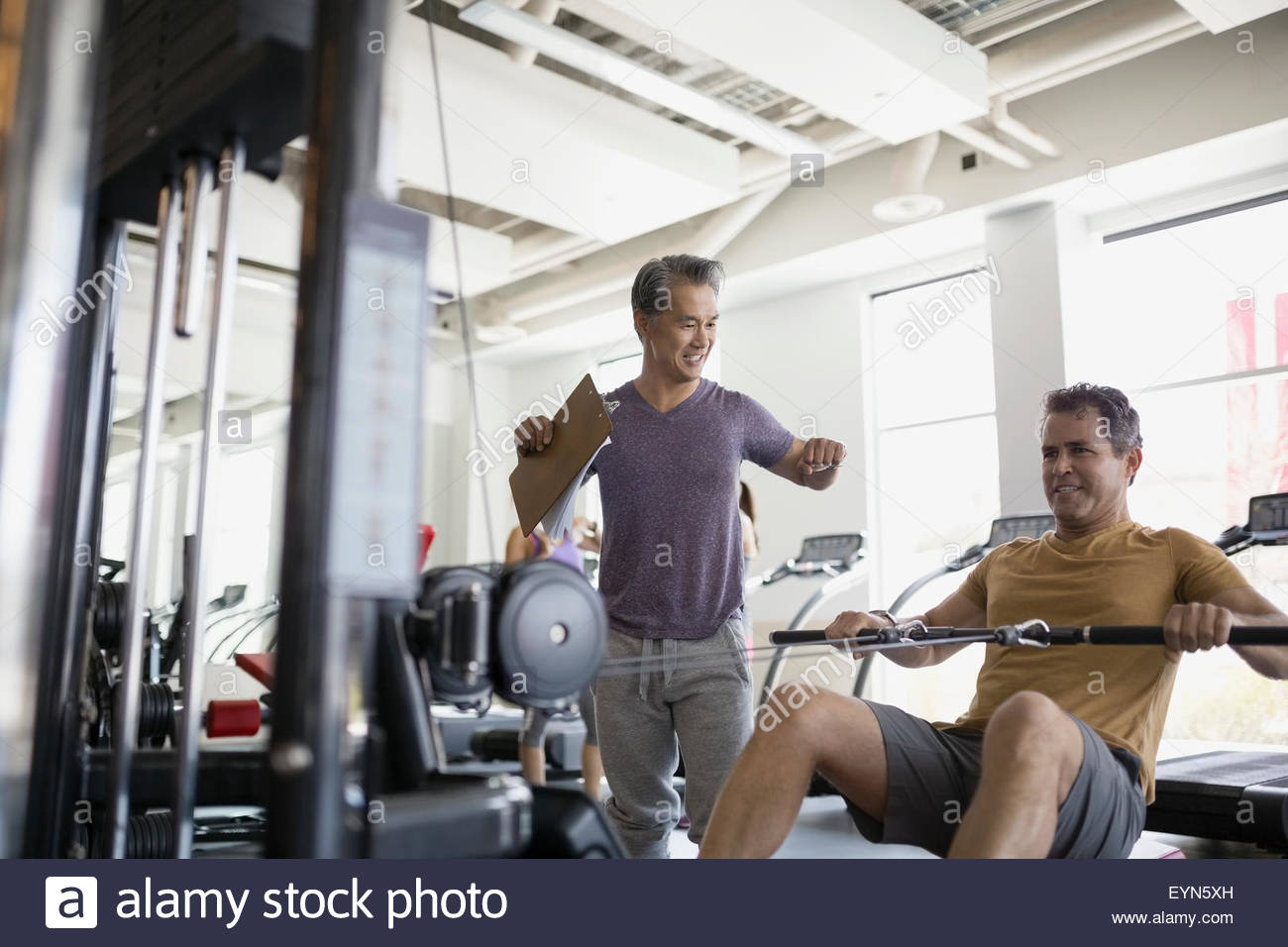 Personal trainer guiding man doing cable rows gym - Stock Image