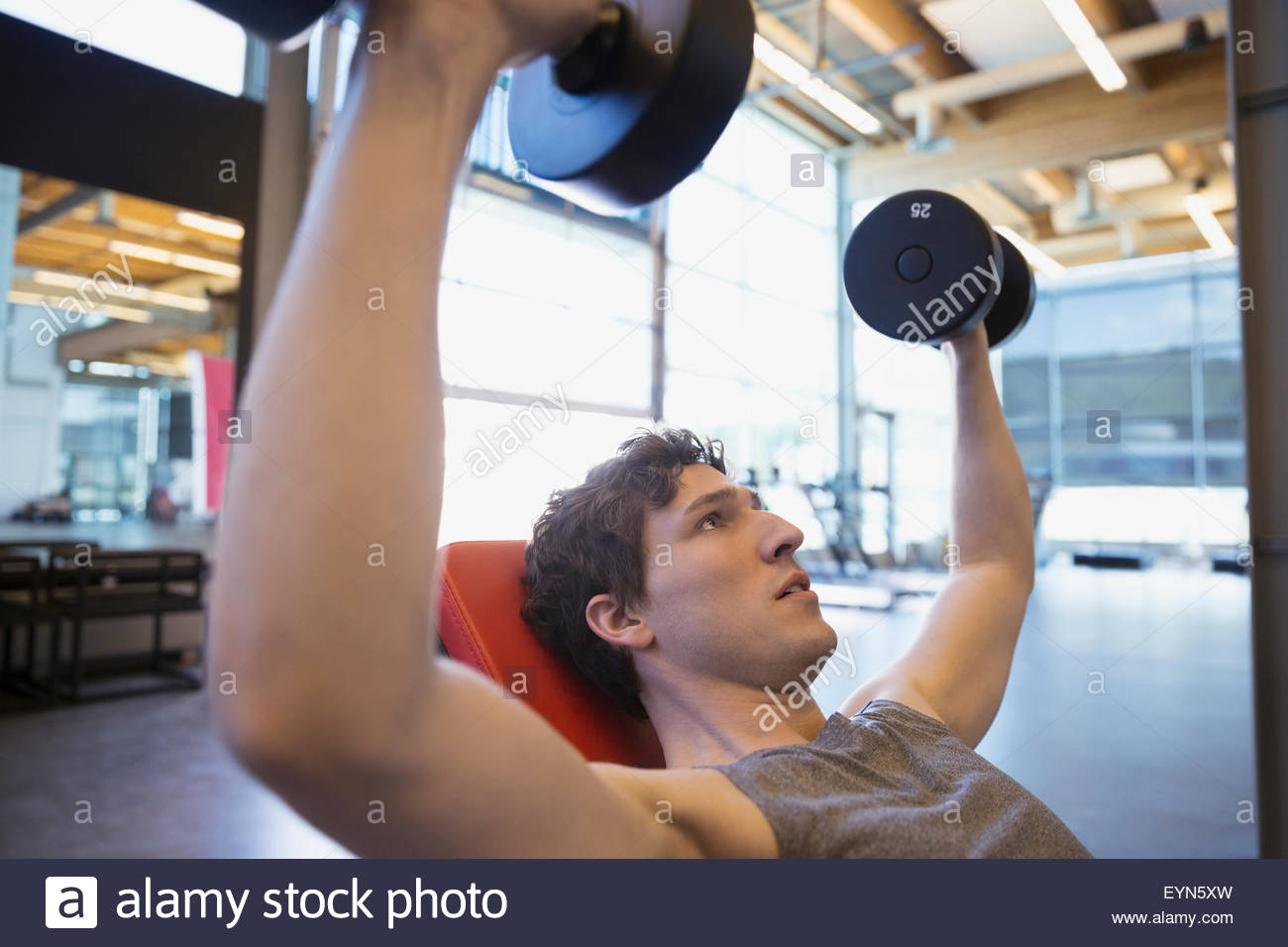 Man doing incline dumbbell chest press at gym - Stock Image