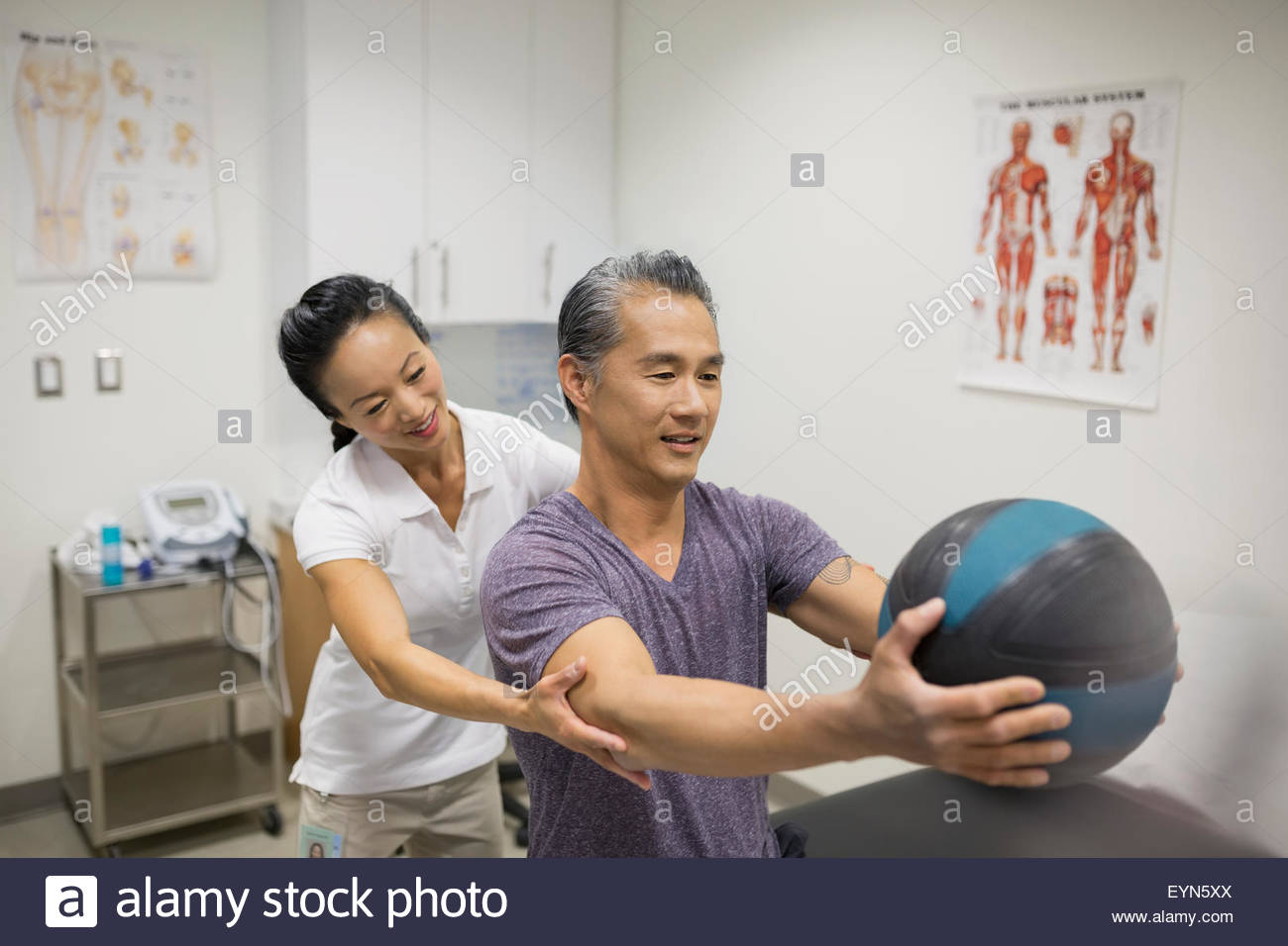 Physical therapist guiding patient holding medicine ball - Stock Image