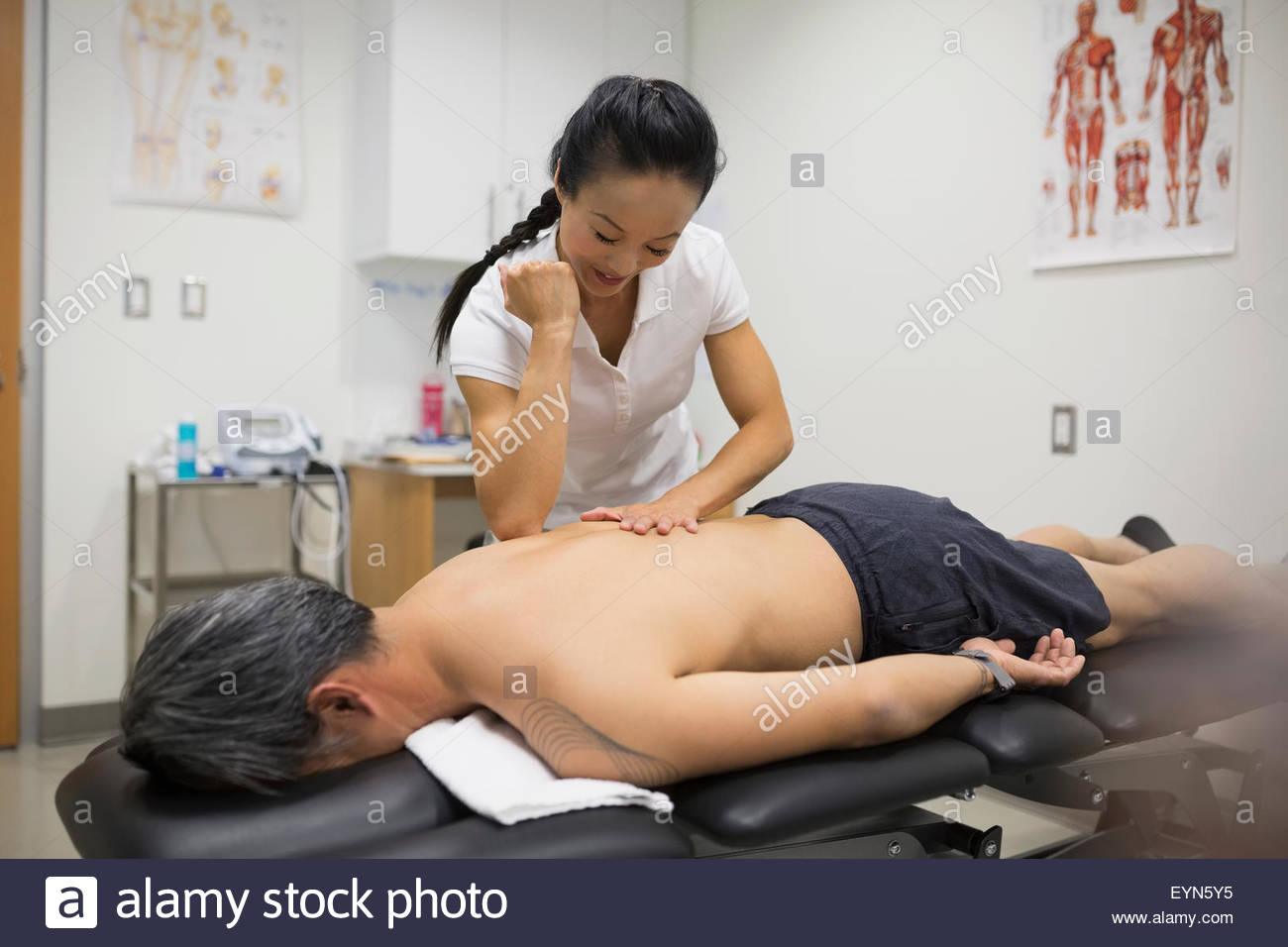 Physical therapist using elbow to massage patient back - Stock Image