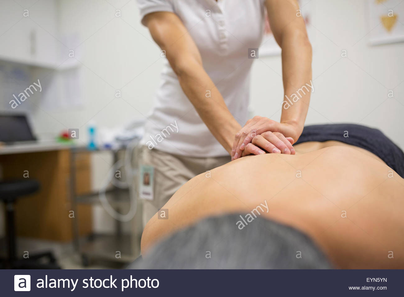 Physical therapist massaging patient back - Stock Image