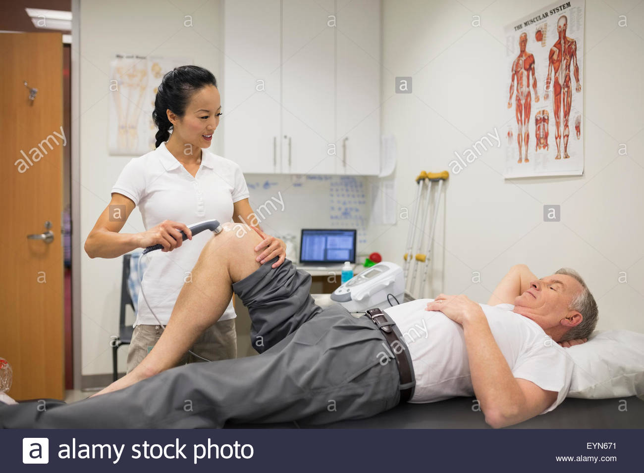 Physical therapist using ultrasound probe on patient knee Stock Photo