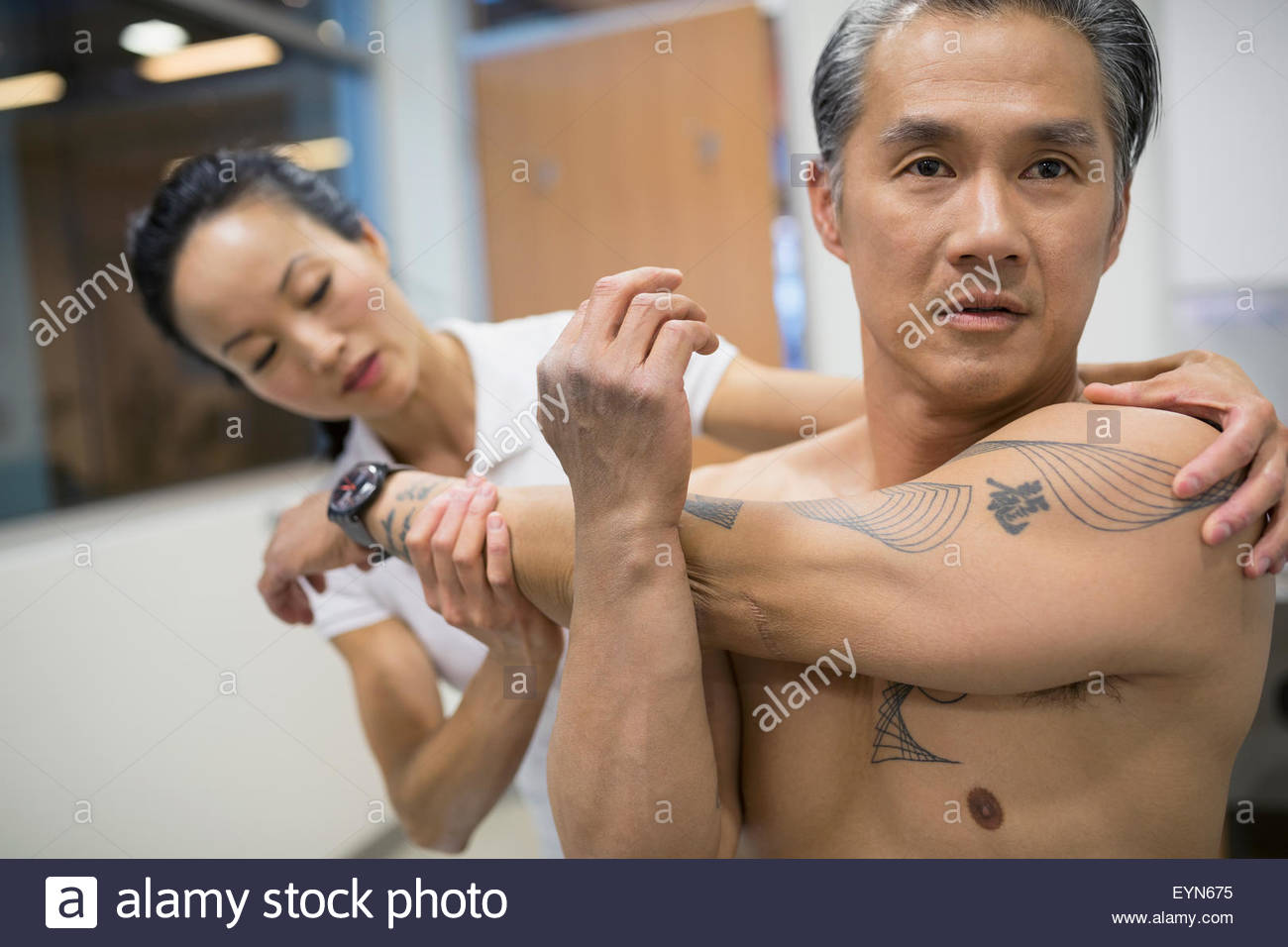 Physical therapist guiding patient stretching arm - Stock Image