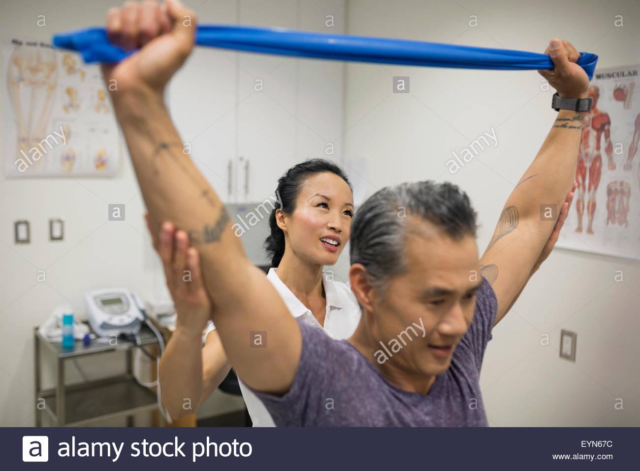 Physical therapist guiding patient pulling resistance band - Stock Image