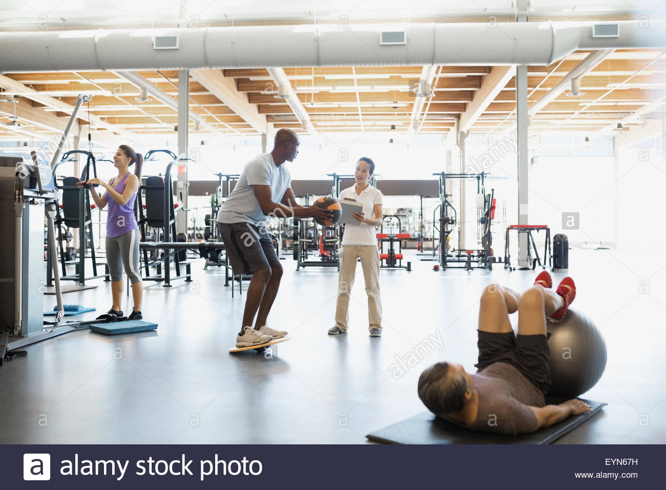 Physical therapist guiding patient with medicine ball gym - Stock Image