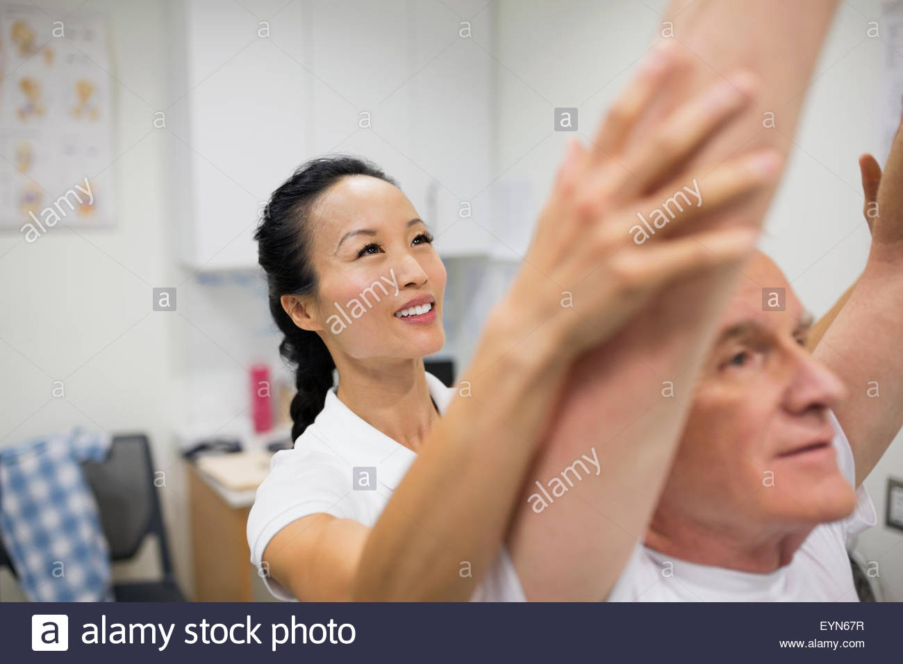 Physical therapist guiding patient with arms raised - Stock Image