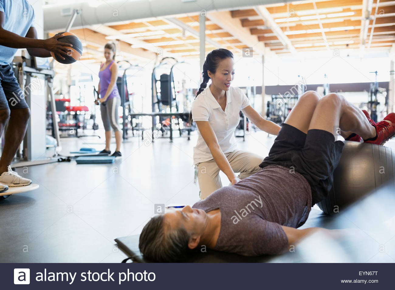Physical therapist guiding patient fitness ball bridge pose - Stock Image