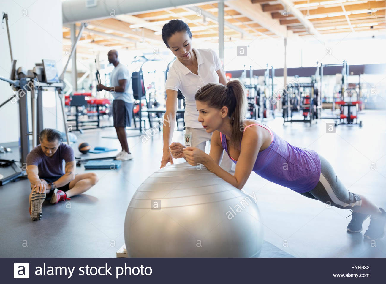 Physical therapist guiding patient holding fitness ball plank - Stock Image