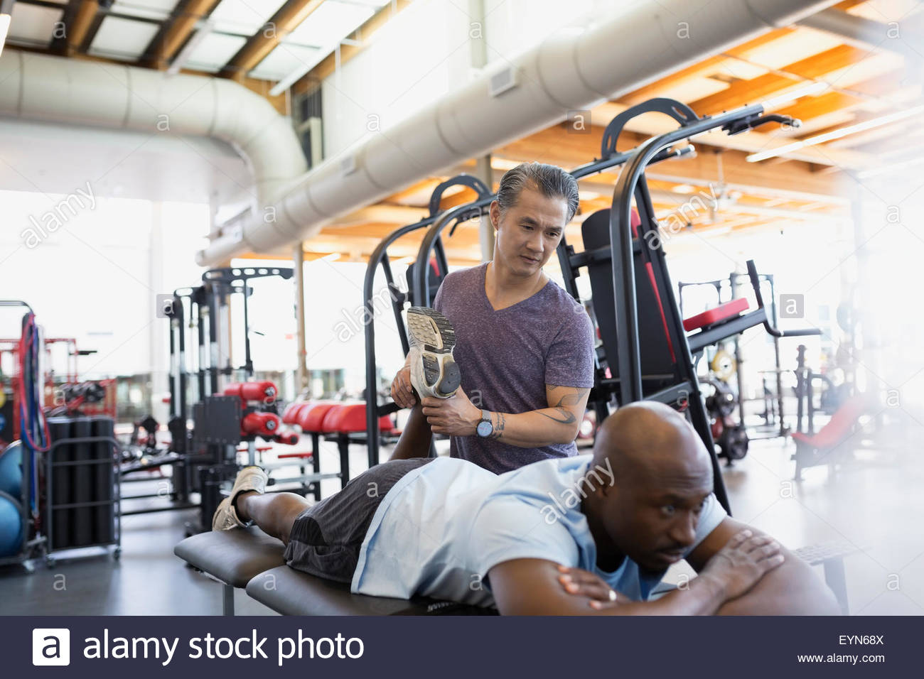 Physical therapist stretching patient leg at gym - Stock Image