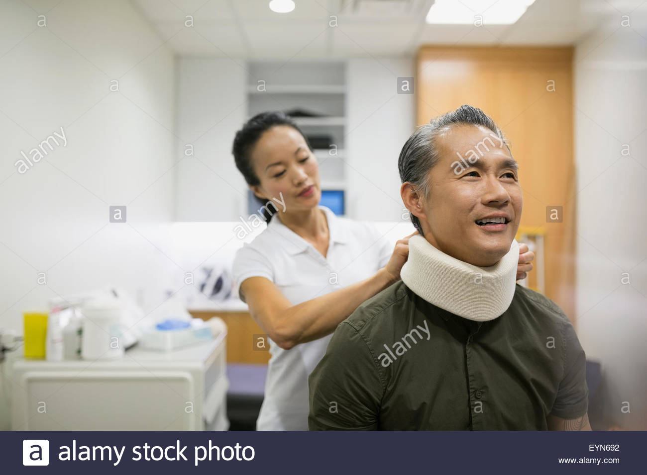 Physical therapist placing neck brace on patient - Stock Image