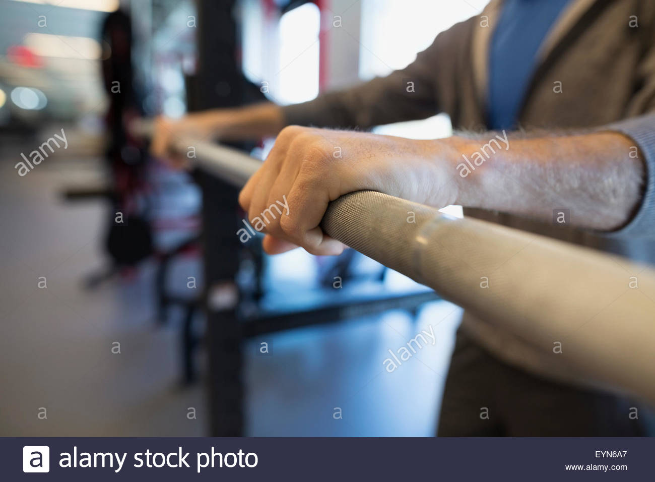Close up man gripping barbell at gym - Stock Image