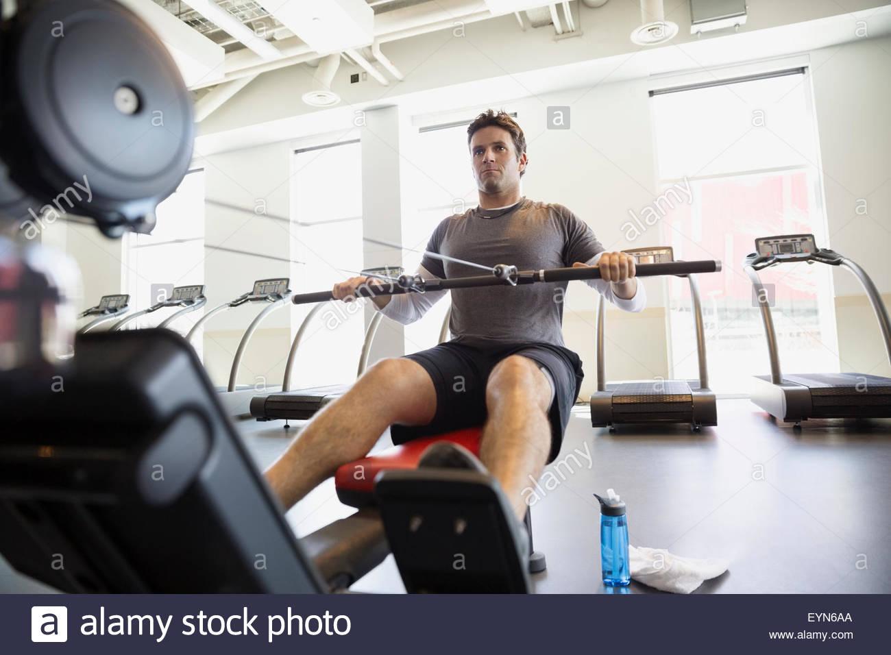 Man using rowing machine at gym - Stock Image
